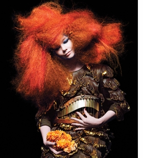 """Featured image is the cover photo for <I>Biophilia</I>, 2011, featuring a red nebula-style wig by Eugene Souleiman, a dress by Iris van Herpen, and a """"harp-belt"""" in cherry wood and bronze by threeASFOUR. Constellation by M/M (Paris). Photo courtesy Inez van Lamsweerde & Vinoodh Matadin."""
