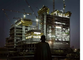 "Featured image, ""Darth Vader, Dubai,"" 2009, is reproduced from French photographer Cédric Delsaux's delightfully surprising new monograph, <a href=""9782915173703.html"">Dark Lens</a>. Treated to a glowing full-page review in the December 11 <a href=""blog-dark-lens-press.html"">New York Times</a>, the work ""wasn't born to pay homage to R2-D2, Luke Skywalker and their buddies,"" according to <a href=""http://www.nytimes.com/2011/12/11/arts/design/cedric-delsauxs-photographs-of-star-wars-on-earth.html"" target='new'>The Times'</a> Dana Jennings. ""'My first intention wasn't to produce a series on <I>Star Wars,</I> but to photograph locations that are the makeup of our modernity: parking lots, peripheral zones, wastelands, forgotten places, of both beauty and ugliness, common and mad,' Mr. Delsaux said by e-mail. 'Nevertheless, something was missing, my images were flat, déjà vu. I then had the idea to add these sci-fi characters, with the immediate effect of making my primal sensations stand out, the fantastical nature of the characters invading the whole frame, both universes harmoniously coming together.'"""