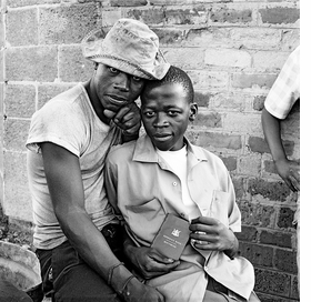 """Featured image, captioned, """"Young men with dompas, the identity document that every African over the age of 16 years had to carry,"""" White City, Jabavu, Soweto, November 1972, is reproduced from 'David Goldblatt: Structures of Dominion and Democracy.'"""