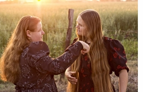 """Featured image is reproduced from <a href=""""9788415303336.html"""">Eunice Adorno: Las Mujeres Flores</a>. """"Hair combing at sunset. Every Thursday afternoon, young people gather on the fields, around the crops and nearby the houses. Nuevo Ideal, Durango, Mexico, 2010"""""""