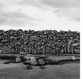 """Featured image, Mariana Cook's <i>Limestone Field, Inis Meáin, Ireland</i> is reproduced from <a href=""""9788862081696.html"""">Stone Walls</a>. Cook writes, """"The spaces in this lace wall allow strong sea winds to pass through without knocking the wall down."""""""
