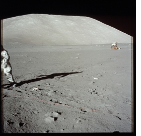 """Harrison """"Jack"""" Schmitt as he deploys the SEP (Surface Electrical Properties) transmitter, part of the Apollo Lunar Surface Experiments Package (ALSEP). Photo by Eugene """"Gene"""" Cernan. [Apollo 17], reproduced from 'The Moon 1968–1972.'"""
