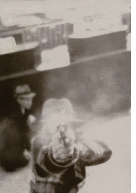 Featured image, of an unknown bank robber shooting at a security camera, is reproduced from <I>The Plot Thickens</I>.