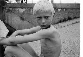 """Over the course of three summers, from 2005 to 2008, New York photographer Yelena Yemchuk returned to her childhood home of Kiev, Ukraine, to document the scene at Gidropark, the Dnieper River recreational complex built """"for the people"""" in 1968. In <a href=""""9788862081603.html"""">Gidropark</a>, her book of black-and-white photographs, Yemchuk captures an uncensored lot enjoying the beaches, overgrown lawns and primitive bodybuilding equipment in various stages of undress. Featured image is reproduced from <a href=""""9788862081603.html"""">Yelena Yemchuk: Gidropark</a>."""