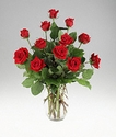 One dozen red roses in a clear vase.