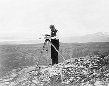 Surveyor Using Theodolite in Alaska Photo Print for Sale