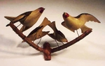Antique American carved folk art birds on branches.