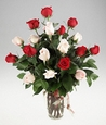 A vase of pink and red roses.