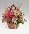 Assorted flowers in a basket arrangement.