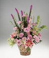 Pink and lavender flowers in a handled basket.
