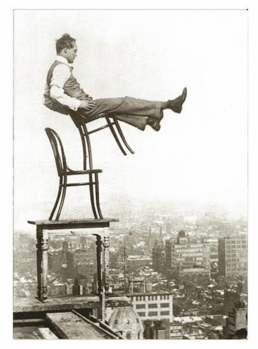 Man Balancing On Chairs