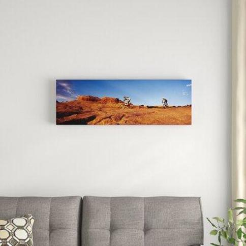 "East Urban Home 'Two People Mountain Biking Moab Utah USA' Photographic Print on Canvas FTCI8485 Size: 12"" H x 36"" W x 1.5"" D"
