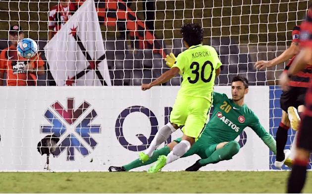Shinzo Koroki of Japan's Urawa Red Diamonds scores past Western Sydney Wanderers goalkeeper Vedran Janjetovic (R) during an AFC Champions League match in Sydney on February 21, 2017
