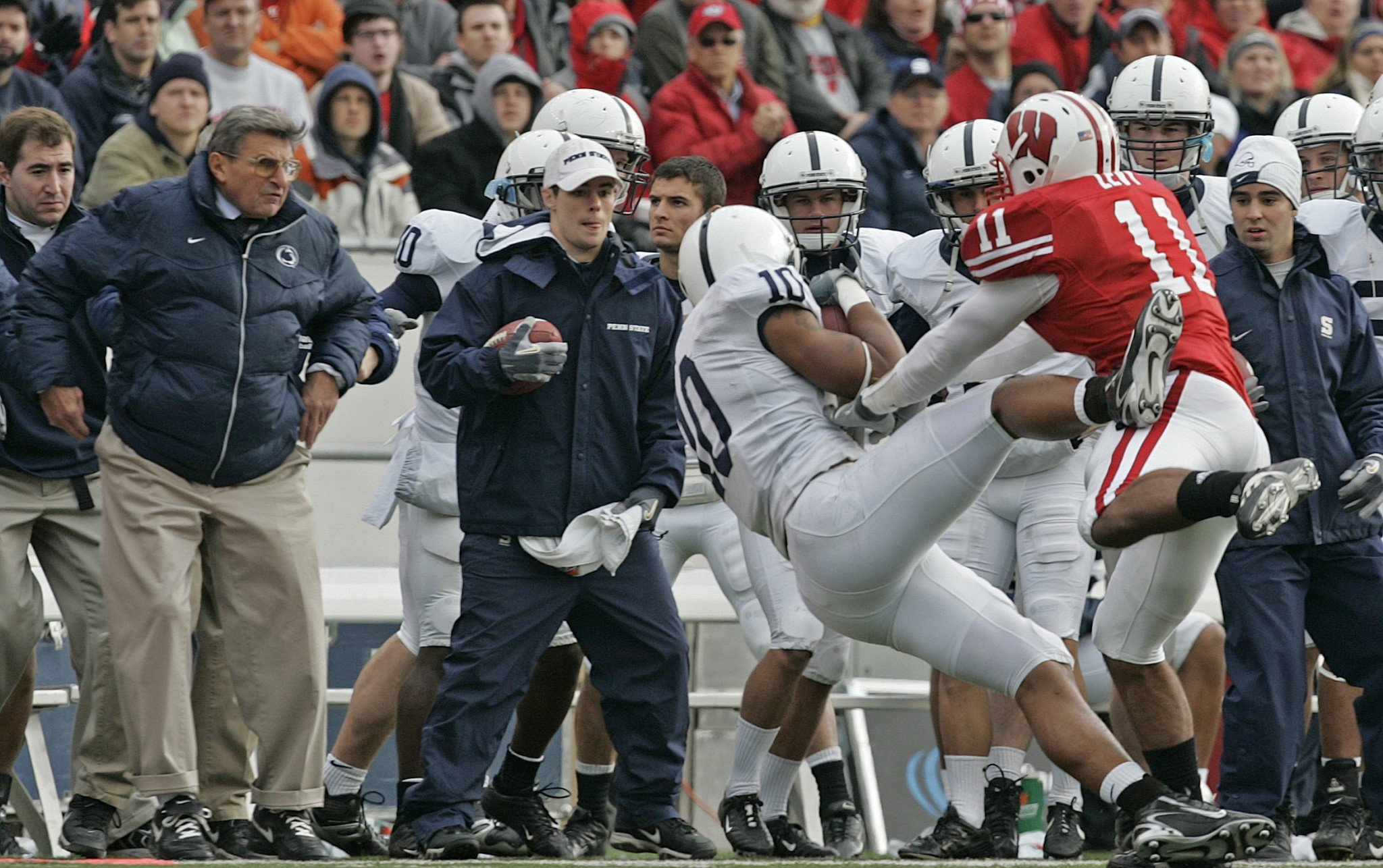 Penn State coach Joe Paterno, left, watches as Wisconsin's DeAndre Levy (11) knocks Penn State's Andrew Quarless out-of-bounds during the second half of a football game against Wisconsin Saturday, Nov. 4, 2006, in Madison, Wis. Paterno was hurt on the play and left the game. (AP Photo/Andy Manis)