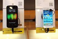 A Samsung Galaxy Nexus phones (L) is seen on display at a Sprint store, on April 27, in San Francisco, California. A judge on Friday granted Apple's request for an injunction blocking US sales of Samsung Galaxy Nexus, made in collaboration with Google to challenge the iPhone