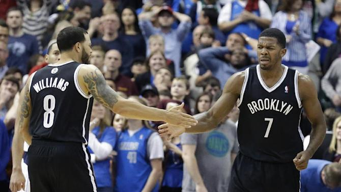 Brooklyn Nets guard Joe Johnson (7) gets a congratulations from teammate  Deron Williams (8) after Johnson scored during the second half of an NBA basketball game against the Dallas Mavericks Sunday, March 23, 2014, in Dallas. The Nets won 107-104 in overtime