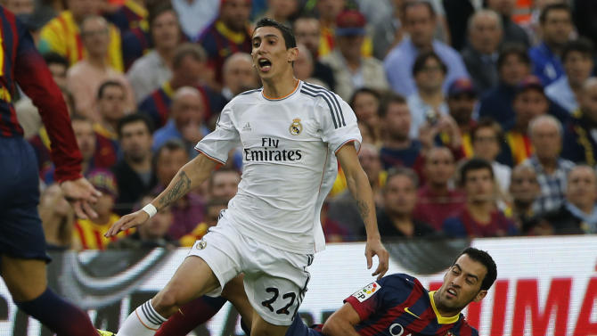 Barcelona's Sergio Busquets challenges for the ball with Real Madrid's Angel Di Maria from Argentina during a Spanish La Liga soccer match between Barcelona F.C. and Real Madrid at the Camp Nou stadium in Barcelona, Spain,  Saturday, Oct. 26, 2013