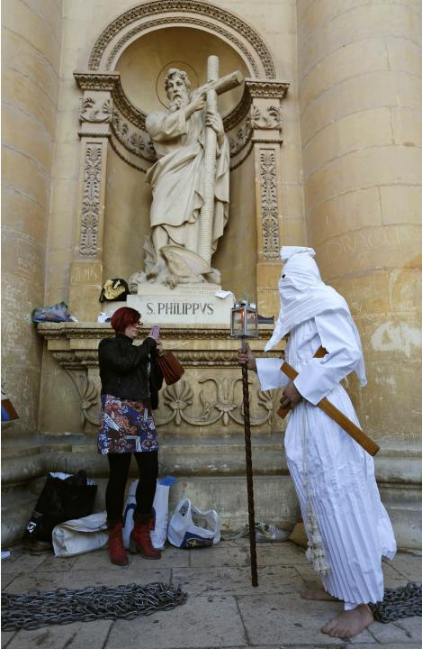 A hooded penitent with chains attached to his ankles is photographed by his partner before taking part in a Good Friday procession outside the Rotunda of Mosta, in Mosta