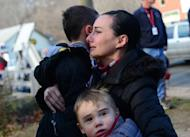 A mother hugs her children after paying tribute to the victims of an elementary school shooting in Newtown, Connecticut, on December 15, 2012. Most of the 26 people gunned down at a Connecticut elementary school received multiple gunshot wounds from a assault rifle, the Connecticut chief medical examiner said Saturday
