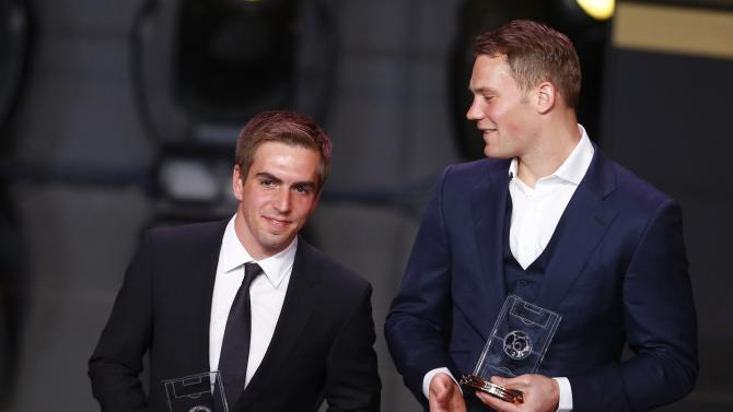 Bayern Munich defender Philipp Lahm and goalkeeper Manuel Neuer hold their awards after being named as members of the Team of the Year at the FIFA Ballon d'Or ceremony in Zurich