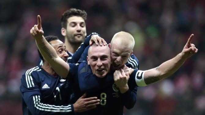 Brown of Scotland celebrates with his teammates after scoring a goal against Poland during their international friendly match in Warsaw
