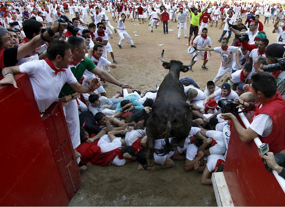 A wild cow leaps over revellers into the bull ring after the sixth running of the bulls of the San Fermin festival in Pamplona