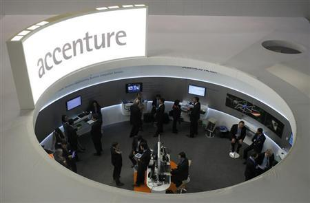 Visitors look at devices at Accenture stand at the Mobile World Congress in Barcelona, February 26, 2013 file photo. REUTERS/Albert Gea