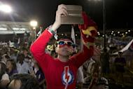 A supporter of the ruling People's Action Party takes a photograph as he waits to hear from Singapore Prime Minister Lee Hsien Loong in Singapore, Saturday, Sept. 12, 2015. The party that has ruled Singapore since it became a country a half-century ago appeared poised to stay in power for five more years as the city-state's citizens voted Friday in a compulsory election. (AP Photo/Ng Han Guan)