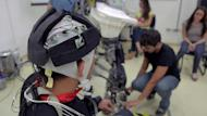 Undated handout picture showing a paraplegic patient (L) wearing an interface helmet being prepared for a test at Brazilian scientist Miguel Nicolelis' lab in Sao Paulo, Brazil