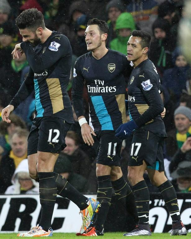 Arsenal's Mesut Ozil (C) celebrates with teammate Alexis Sanchez (R) after scoring the opening goal of the Premier League match against Norwich City at Carrow Road on November 29, 2015