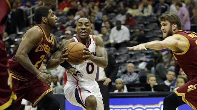 Atlanta Hawks' Jeff Teague, center, drives to the basket between the defense of Cleveland Cavaliers' Kyrie Irving, left, and Spencer Hawes in the first quarter of an NBA basketball game, Friday, April 4, 2014, in Atlanta