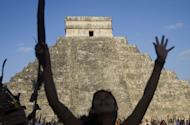 Visitors raise their hands during celebrations for the end of the Mayan cycle known as Bak'tun 13 and the start of the Maya new age, at the Chichen Itza archaeological park, in Yucatan state, Mexico on December 21, 2012. A global day of lighthearted doom-themed celebration and superstitious scare-mongering culminated at the temples of the Mayan people, whose calendar sparked fears of apocalypse