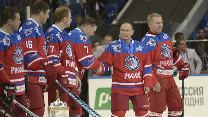 Putin and retired ice hockey players line up during a gala game opening a new season of the Night Ice Hockey League in Sochi