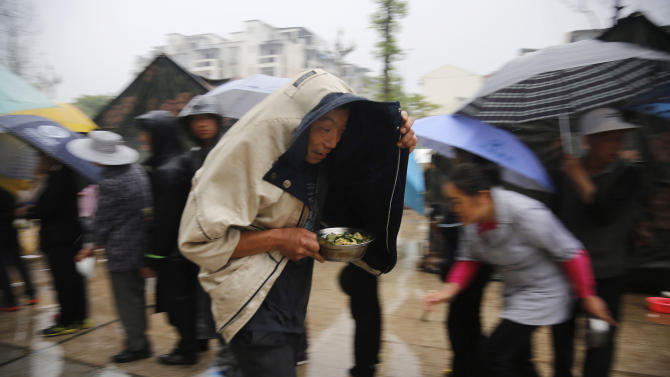 A man collects meal during a ration in the rain in the county seat of Lushan in southwestern China's Sichuan province, Tuesday, April 23, 2013. The efforts under way in the mountainous province after a quake Saturday that killed nearly 200 people showed that the government has continued to hone its disaster reaction — long considered a crucial leadership test in China — since a much more devastating earthquake in 2008, also in Sichuan, and another one in 2010 in the western region of Yushu. (AP Photo)