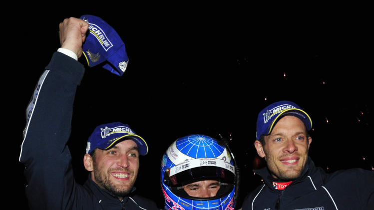 Peugeot drivers, from left, Franck Montagny and Stephane Sarrazin, of France, and Alexander Wurz, of Austria, celebrate after winning the American Le Mans Series' Petit Le Mans auto race at Road Atlanta, Saturday, Oct. 1, 2011, in Braselton, Ga.  (AP Photo/Rainier Ehrhardt)