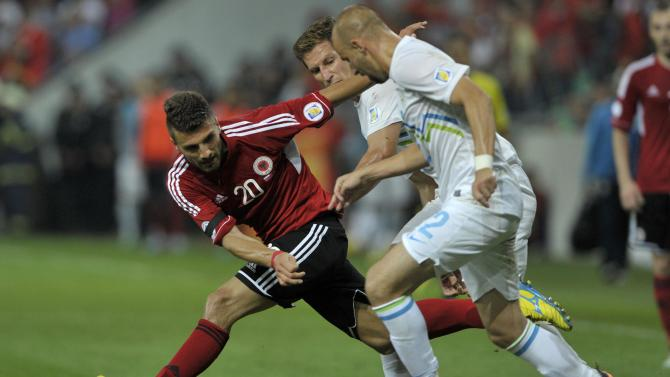 Rama of Albania challenges Brecko of Slovenia during their 2014 World Cup qualifying soccer match in Ljubliana