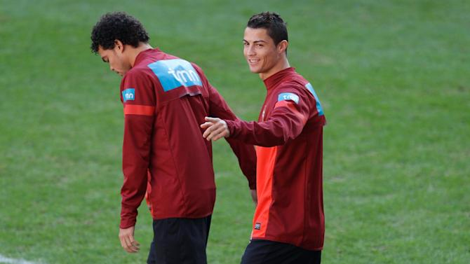 Portugal's Cristiano Ronaldo gestures as he walks onto the pitch with teammate Pepe, left, for a training session Sunday, Nov. 17 2013, at the Luz stadium in Lisbon. Portugal will play Sweden on Tuesday in a World Cup qualifying playoff second-leg soccer match