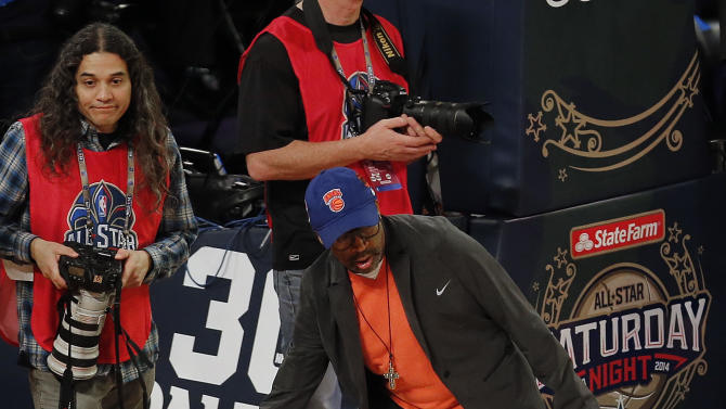 Director Spike Lee grabs a loose ball during the skills competition at the NBA All Star basketball game, Saturday, Feb. 15, 2014, in New Orleans. (AP Photo/Bill Haber)
