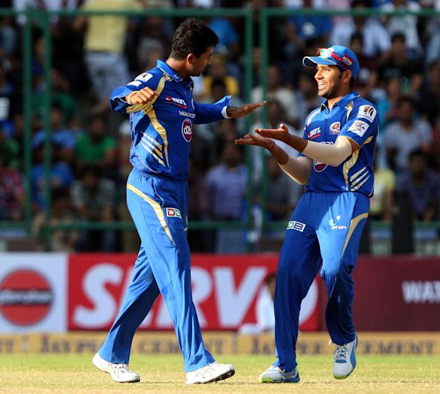 Pragyan Ojha and Rohit Sharma celebrates fall of Ashton Agar's wicket during the CLT20 match between Perth Scorchers and Mumbai Indians at Feroz Shah Kotla, Delhi on Oct. 2, 2013. (Photo: IANS)