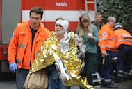 Czech rescue workers help a woman who was injured in the blast in Parague's historic centre on April 29, 2013. A powerful blast has ripped through a multi-storey building in Prague's historic centre, injuring about 40 people, rescuers said, adding that some people may be buried in the rubble