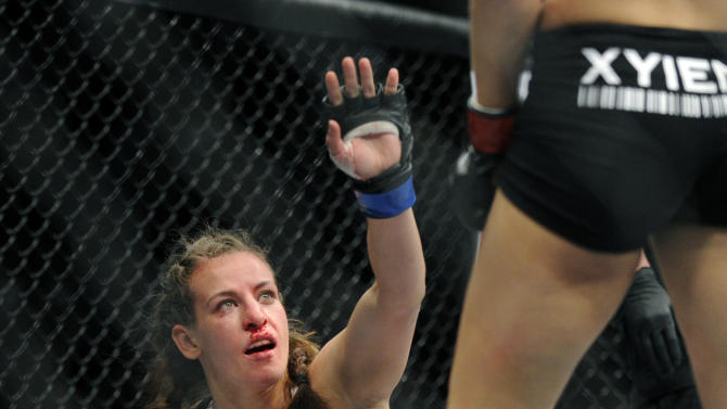 Miesha Tate of Yakima, Wash., gestures to Ronda Rousey of Venice, Calif., during the UFC 168 mixed martial arts middleweight championship bout during the UFC 168 mixed martial arts women's bantamweight title fight on Saturday, Dec. 28, 2013, in Las Vegas. Rousey won by a third round tap out. (AP Photo/David Becker)