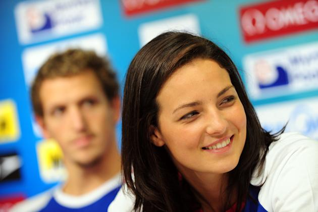Britain's swimmer Keri-Anne Payne smiles next to Britain's competitor Adam Brown (L) during a press conference at the indoor stadium of the Oriental Sports Center during the FINA World Champio