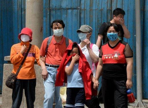 People wear masks to protect against air pollution and dust in Beijing on May 19. China vowed Thursday to reduce levels of atmospheric pollutants in Beijing and other major cities by as much as 25 percent to try to improve their dire air quality