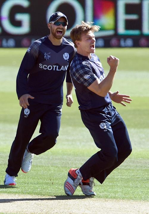 Scotland's Richie Berrington (R) celebrates with teammate Preston Mommsen (L) after dismissing Afghanistan's Afsar Zazai during their Cricket World Cup match in Dunedin on February 26, 2015