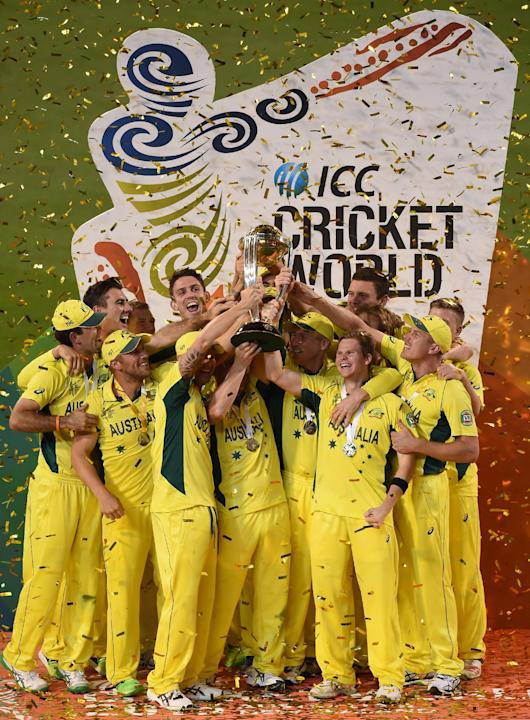 Australian captain Michael Clarke holds the trophy with his teammates as they celebrate their seven wicket win over New Zealand in the Cricket World Cup final in Melbourne, Australia, Sunday, March 29