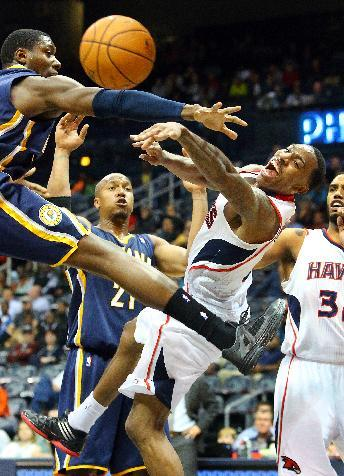 Hawks point guard Jeff Teague is forced to pass it off under the basket by Indiana Pacers center Ian Mahinmi, left, during the second half of a preseason NBA basketball game on Tuesday, Oct. 22, 2013, in Atlanta