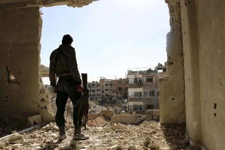A rebel fighter stands on a damaged building near the frontline during what the rebel fighters called a battle to unite rebel factions against forces loyal to Syria's President Assad in Jobar