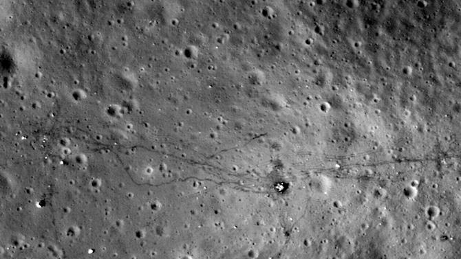 This August 2011 image made available by NASA shows paths left by walking astronauts, single lines, and lunar buggy tracks, parallel lines, from the 1972 U.S. Apollo 17 moon mission. NASA's Lunar Reconnaissance Orbiter made this and other photographs of lunar landing sites from 13 to 15 miles above the moon's surface. (AP Photo/NASA)