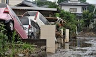 "Vehicles are piled-up in a residential area covered in mud after heavy rains fell at Kumamoto city on Japan's southern island of Kyushu. Southwestern Japan was bracing for more torrential rain on Friday, on top of ""unprecedented"" downpours that left at least 19 people dead and eight missing as whole neighbourhoods were swamped"