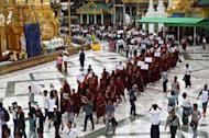 Ethnic Rakhine demonstrators and Buddhist monks hold signs as they gather at the Shwedagon pagoda after unrest flared in the western Myanmar state. Security forces have tried to restore order to a Myanmar state placed under emergency rule after a wave of deadly religious violence, as the United Nations evacuated foreign workers